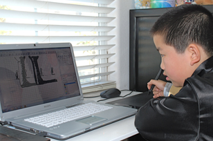 Perry Chen using a laptop and computer tablet to create animation